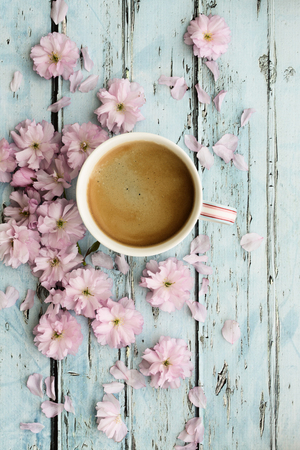 Coffee and pink cherry blossoms on a rustic wooden background Banco de Imagens