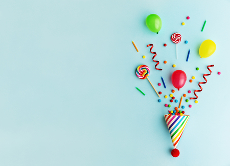 Party hat with candy, balloons and birthday candles