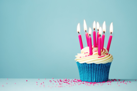 Birthday cupcake with pink candles on a blue background