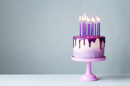 Birthday cake with drip icing and lots of purple candles against a gray background