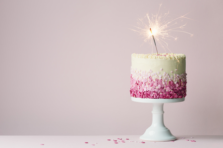 Birthday cake with pink sprinkles and sparkler