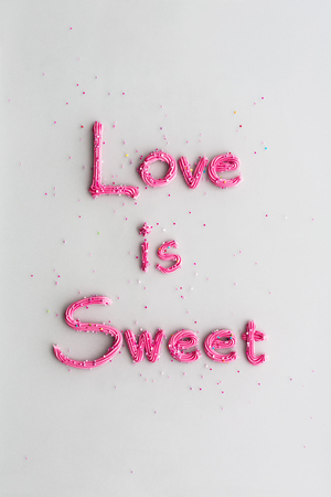 Love is sweet written in buttercream frosting Stock Photo