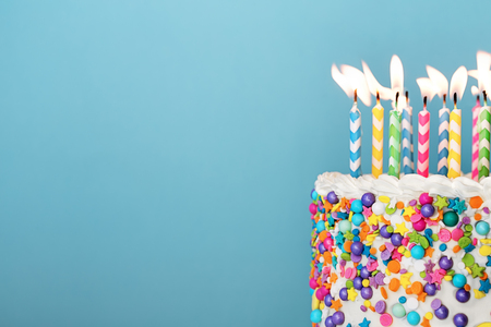 Birthday cake with lots of colorful candles and sprinkles on a blue background Banco de Imagens - 119041436