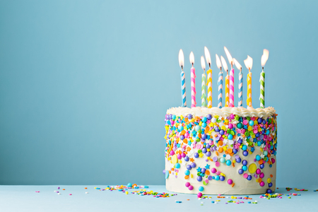 Colorful birthday cake with sprinkles and ten candles on a blue background with copyspace