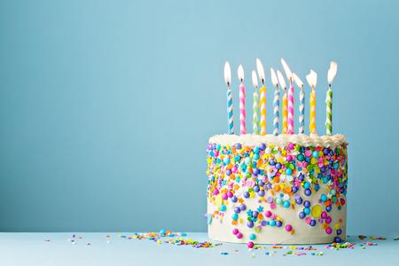Kleurrijke verjaardagstaart met hagelslag en tien kaarsen op een blauwe achtergrond met copyspace