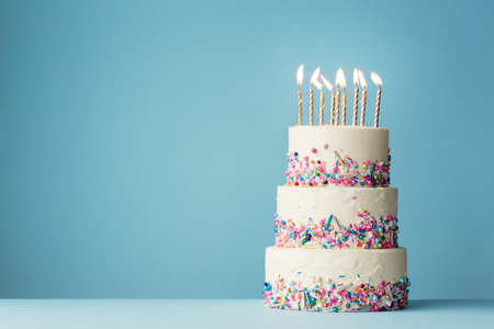 Birthday cake with three tiers and colorful sprinkles Stock Photo