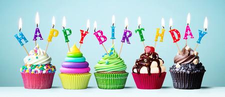 Cupcakes coloridos con velas deletreando feliz cumpleaños Foto de archivo