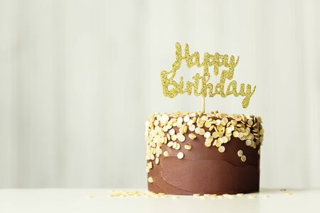 "Chocolate birthday cake with golden ""happy birthday"" sign"