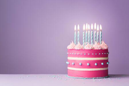 Gâteau d'anniversaire rose avec neuf bougies