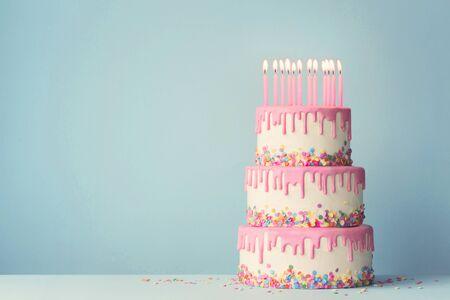Pastel de cumpleaños escalonado con glaseado de goteo y doce velas Foto de archivo