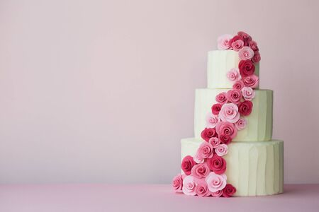 Pastel de bodas escalonado con rosas de pasta de azúcar en rosa