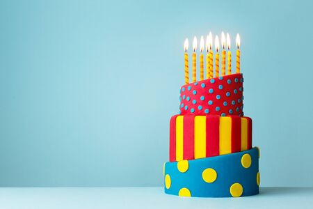 Colorful topsy turvy birthday cake with candles Stock Photo