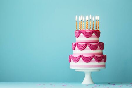 Pink tiered birthday cake with birthday candles