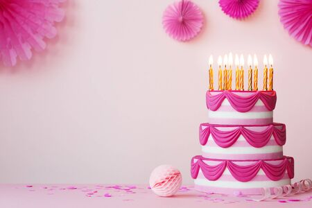 Birthday party with pink tiered birthday cake and golden candles Banco de Imagens
