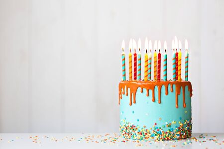 Colorful birthday cake with lots of candles and orange drip icing