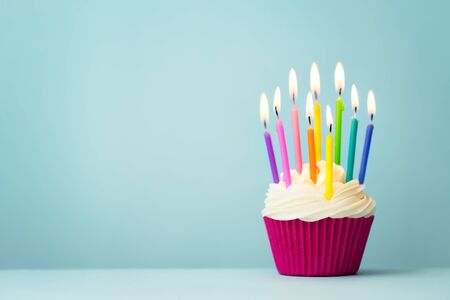 Birthday cupcake with rainbow colored candles