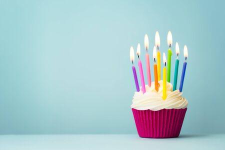 Geburtstagskuchen mit regenbogenfarbenen Kerzen