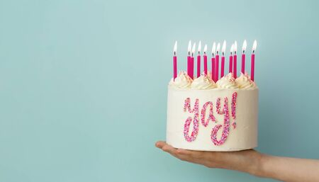 Hand holding birthday cake with pink candles and yay written in sprinkles 스톡 콘텐츠