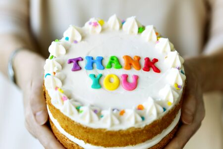 Hands holding cake with colorful rainbow letters spelling thank you Banco de Imagens