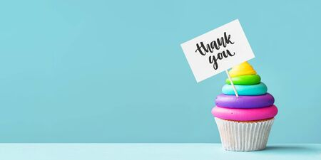Brightly colored rainbow cupcake decorated with a thank you sign