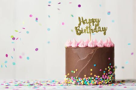 Chocolate birthday cake with happy birthday banner and falling confetti Banco de Imagens