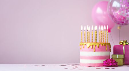 Pink birthday cake with golden candles and balloons Banco de Imagens