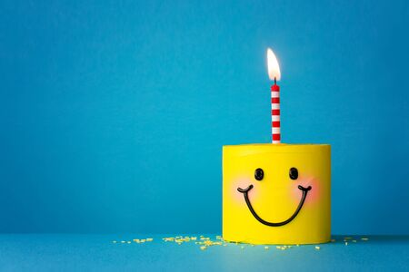 Yellow smiley face birthday cake with one candle Archivio Fotografico