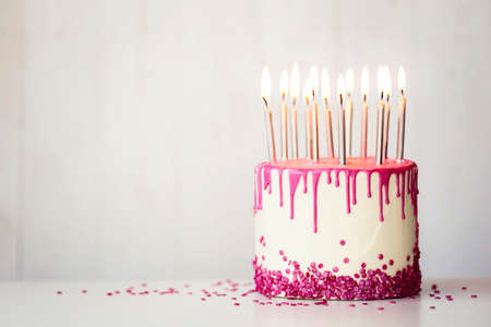 Birthday cake with pink drip icing and birthday candles with copy space to side Zdjęcie Seryjne