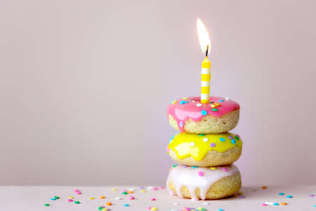 Stack of brightly colored birthday donuts with a candle