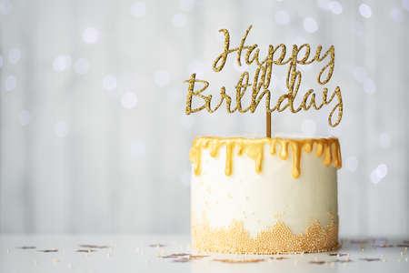 Golden birthday cake with happy birthday sign