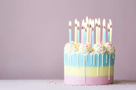 Birthday cake with drip icing and pastel birthday candles Banco de Imagens