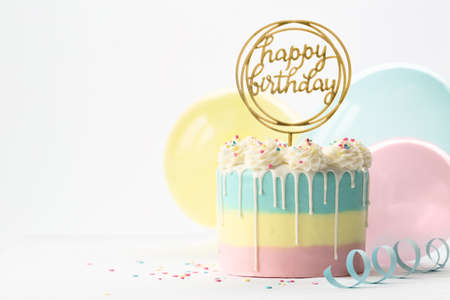 Pastel birthday cake with drip icing and balloons Banco de Imagens
