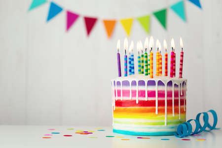 Rainbow birthday cake with colorful candles and drip icing
