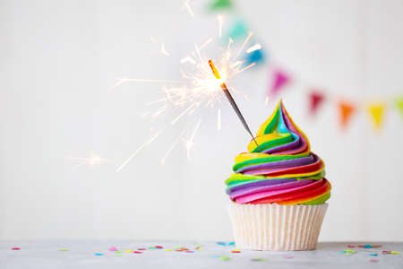 Colorful rainbow cupcake with celebration sparkler