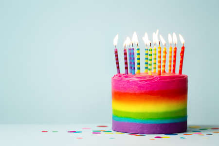 Rainbow colored birthday cake with brightly colored birthday candles