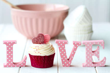 Cupcake decorated with fondant hearts with mixing bowl and love sign