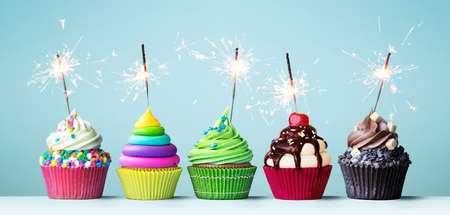 Assortment of brightly colored celebration cupcakes decorated with sparklers for a birthday party Zdjęcie Seryjne