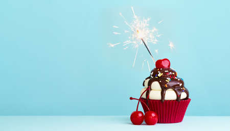 Celebration cupcake with cherry and sparkler