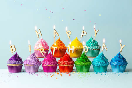 Rainbow colored cupcakes with birthday candles spelling happy birthday Zdjęcie Seryjne