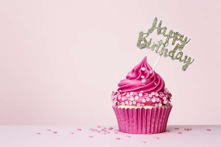 Birthday background with celebration cupcake with happy birthday banner on a pink background