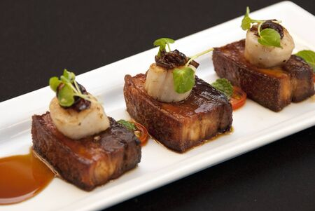 Pork Belly with crackling and Scallops topped with onion and dressed with tomatoes and jus
