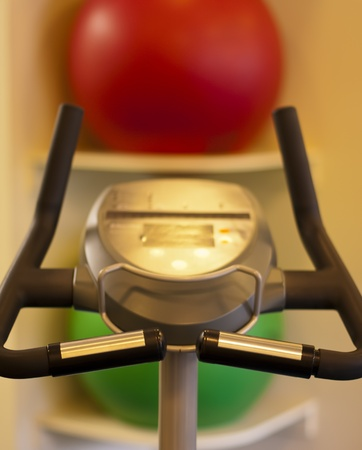Exercise bike in a gym with exercise balls in the background