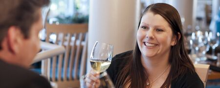 Couple in Restaurant with wine glass and smiling Banco de Imagens