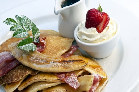 Stack of breakfast pancakes with bacon, banana and maple syrup