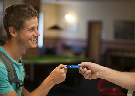 A young man being handed his key in a hostel