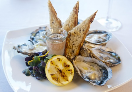 Fresh oysters served on a plate accompanied by lemon, toast and a glass of wine