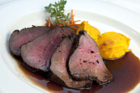 Roast beef served with potatoes and gravy