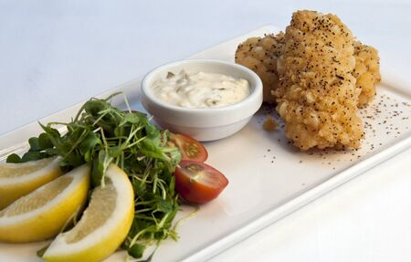 Fried Calamari served on a white dish with a garnish of lemon and tomatoes