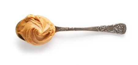spoon of peanut butter isolated on white background, top view