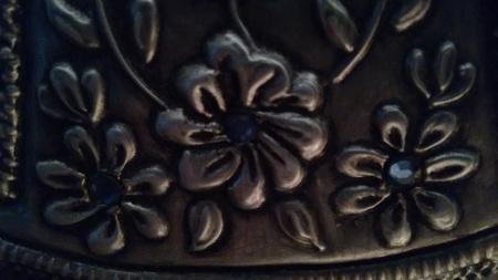 Texture of embossed flowers in metal